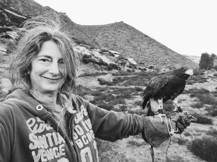 Portrait of smiling woman with hawk against mountains and sky