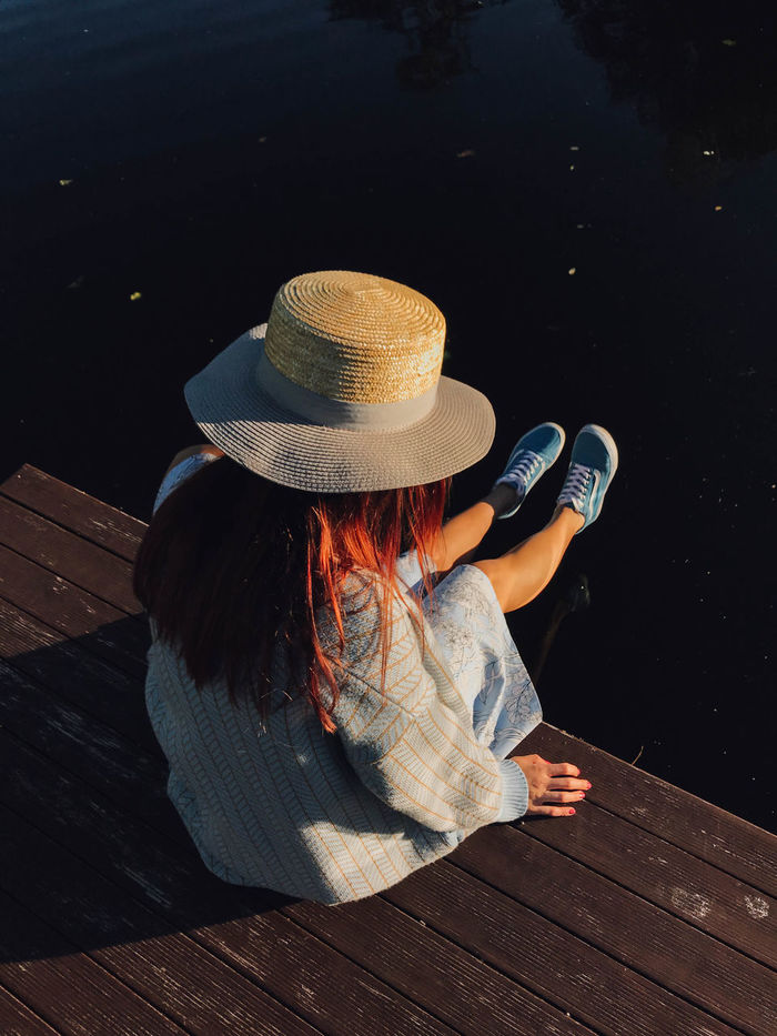REAR VIEW OF WOMAN SITTING BY PIER AT LAKE