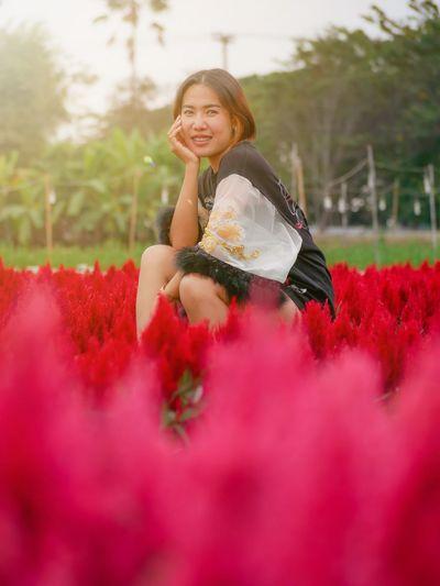 Woman wearing red flower on field