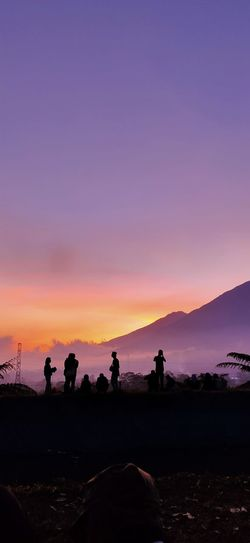 Silhouette people on land against sky during sunset