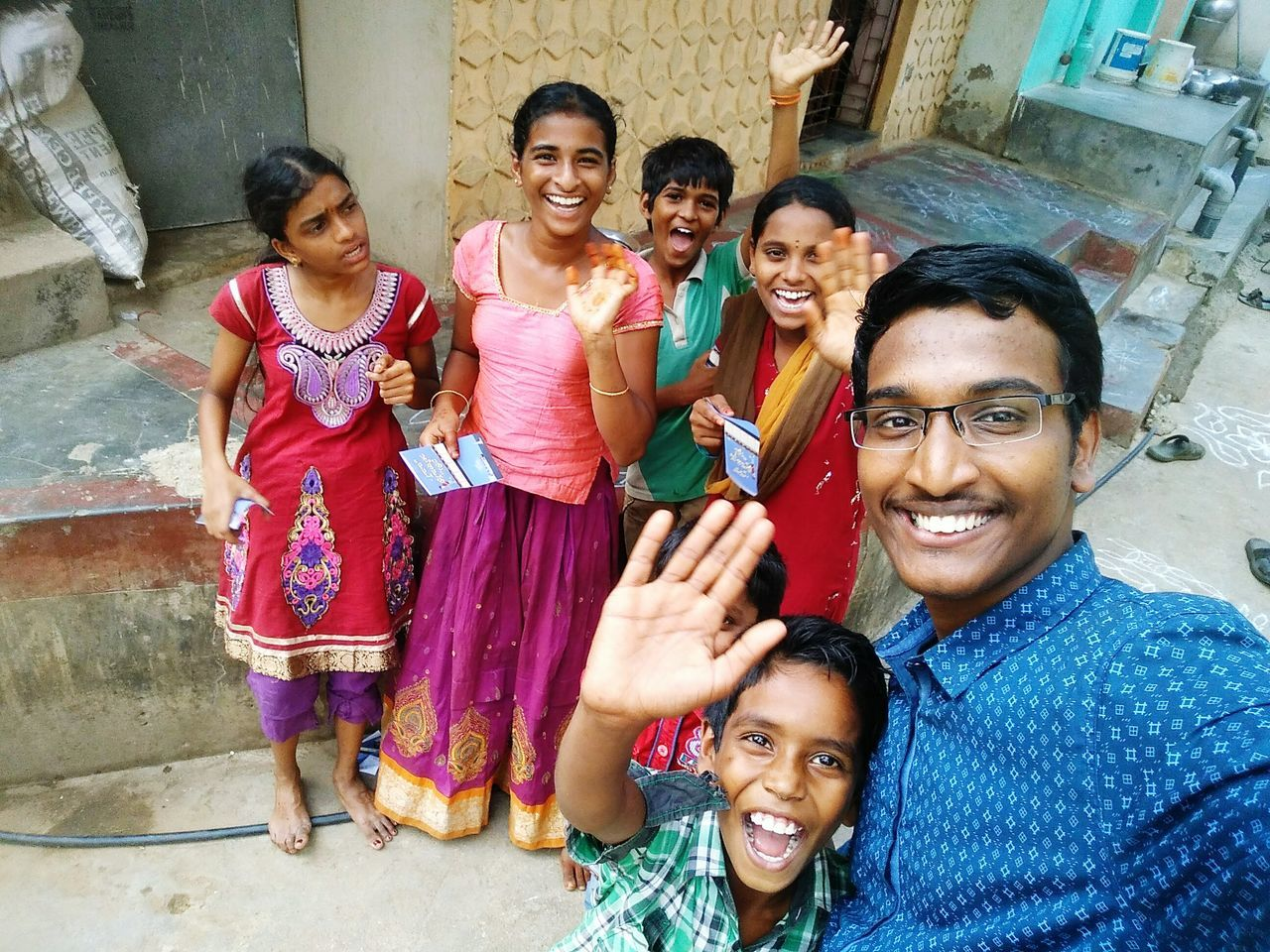 looking at camera, portrait, smiling, boys, happiness, girls, childhood, cheerful, cultures, standing, child, togetherness, built structure, outdoors, real people, architecture, building exterior, young adult, group of people, men, day, eyeglasses, bonding, multi colored, sari, human body part, friendship, adult, holi, people