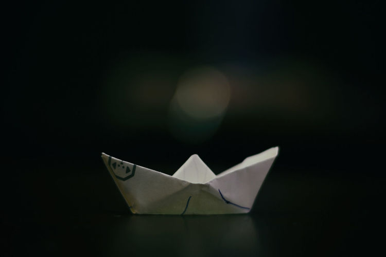 A paper boat seen on a wooden table. Art And Craft Black Background Childhood Close-up Creativity Day Fragility Indoors  Nature No People Paper Paper Boat Single Object Studio Shot
