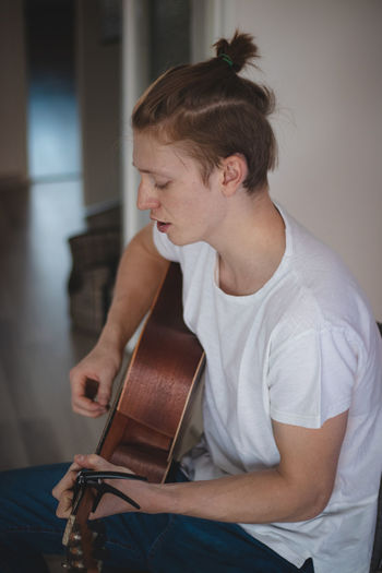 Young man playing guitar at home