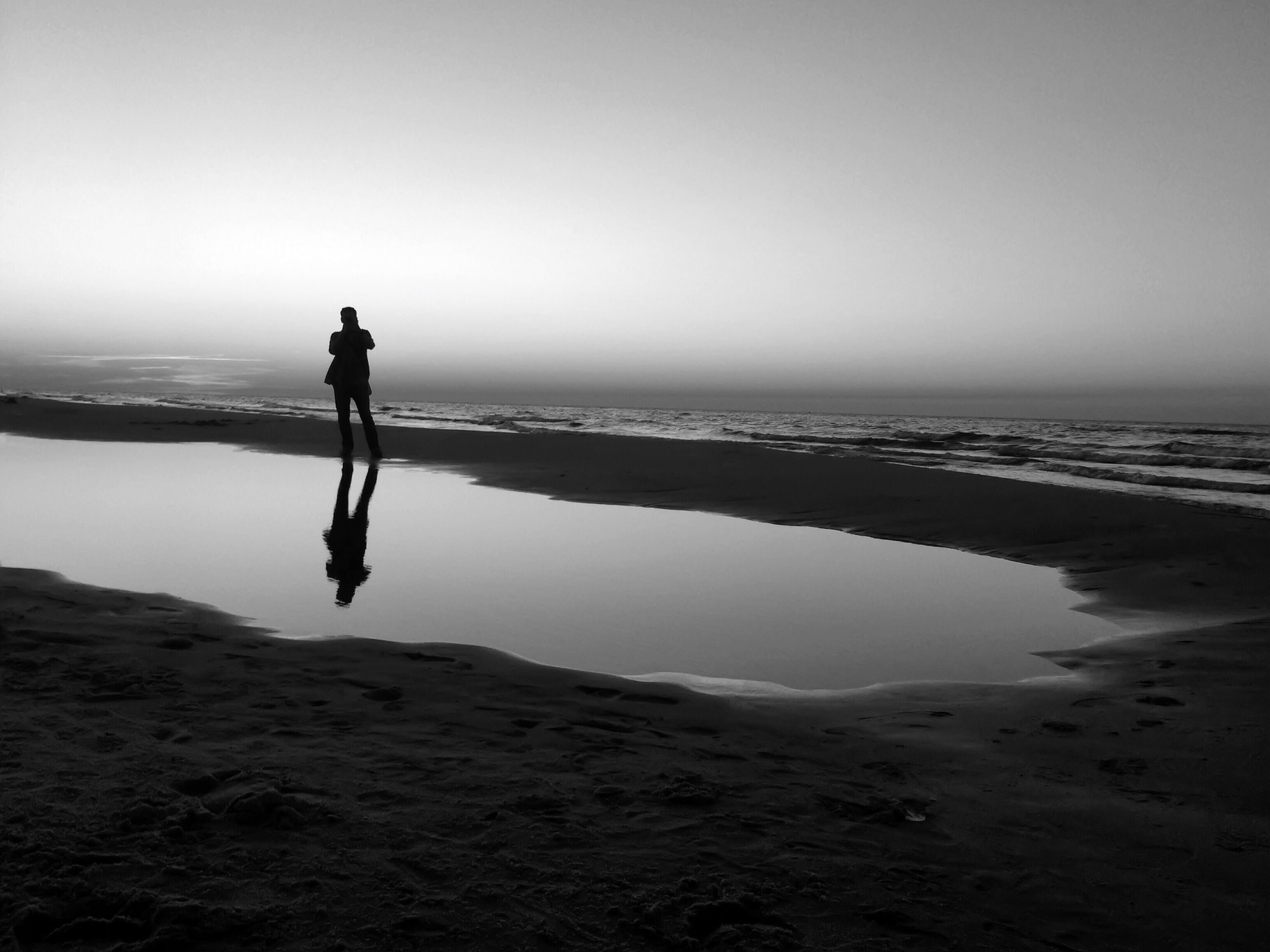 sea, beach, horizon over water, full length, water, shore, sand, standing, lifestyles, leisure activity, copy space, tranquil scene, walking, tranquility, clear sky, rear view, scenics, silhouette