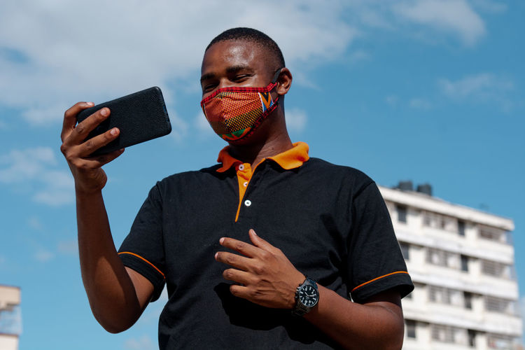 Low angel view of man wearing flu mask holding smart phone against sky