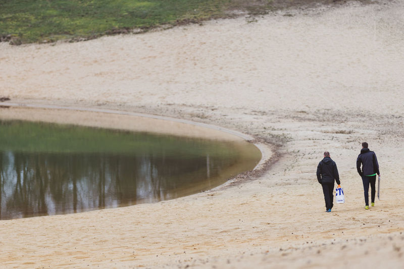 two men walking around at a beach Water Real People Men Leisure Activity Adult Nature Togetherness Walking People Full Length Lifestyles Women Day Rear View Land Sand Beach Outdoors Couple - Relationship Two People Walking Around Lake Reflection Reflections In The Water