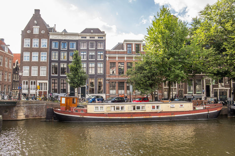 Amsterdam Barge Netherlands Apartment Architecture Building Building Exterior Built Structure Canal Canal House City Day Dutch Houses Holland House Boat Incidental People Mode Of Transportation Nature Nautical Vessel Outdoors Passenger Craft Plant Residential District Row House Tourism Transportation Tree Water