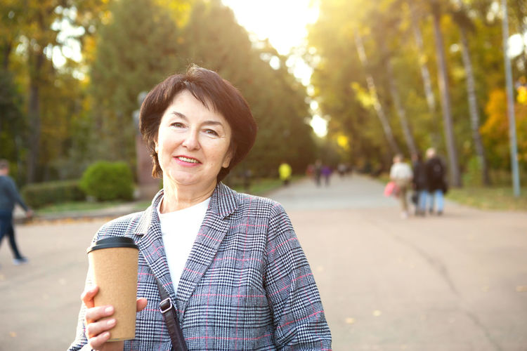 Portrait of smiling woman standing against trees in city