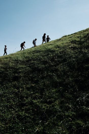 People walking on land against clear sky