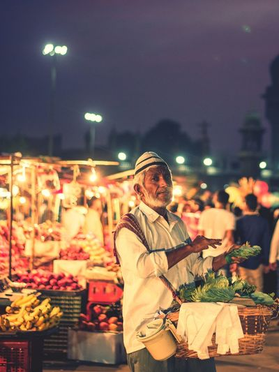 Portrait Of Vendor Selling Beetle Leaves In Illuminated Market At Night