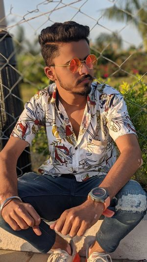 Young man wearing sunglasses sitting outdoors