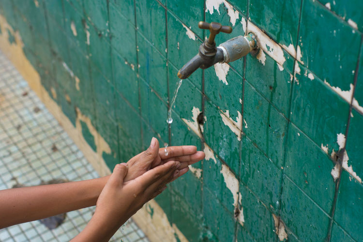 Cropped image of person washing hands in running water outdoors