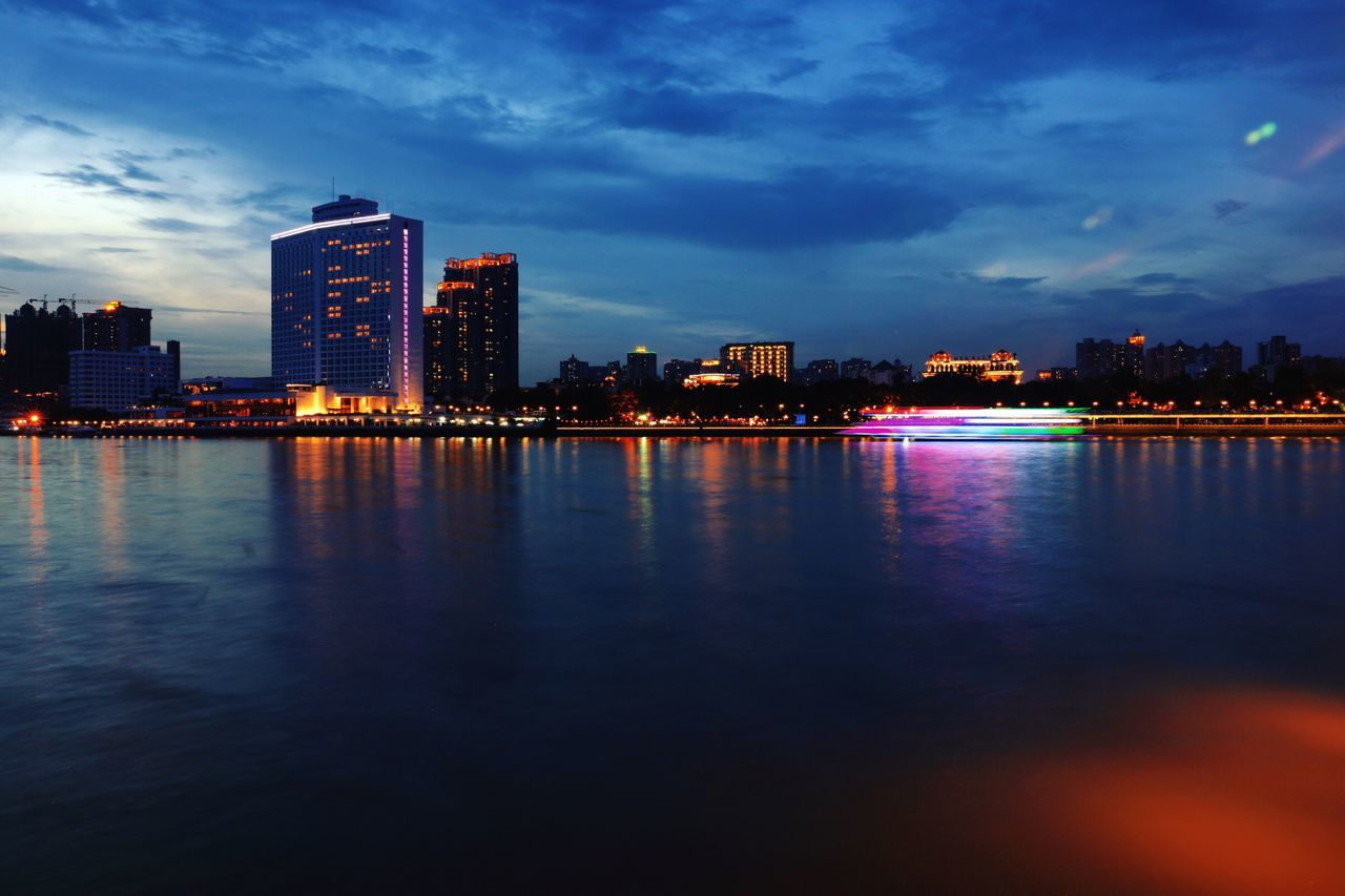 architecture, building exterior, built structure, illuminated, skyscraper, reflection, sky, city, waterfront, water, cityscape, cloud - sky, urban skyline, modern, night, travel destinations, no people, outdoors