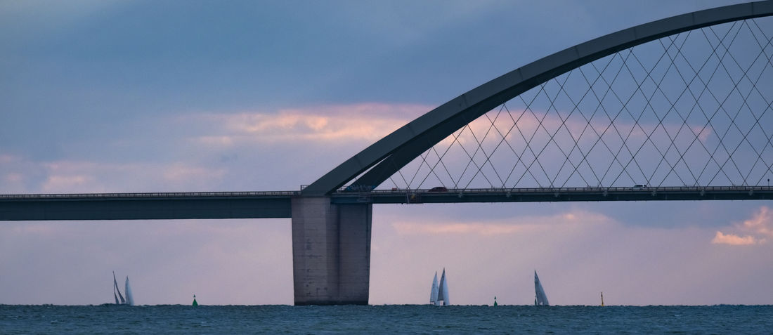 Sunset sailing at the Fehmarnsundbrücke. Fehmarnsundbrücke Schleswig-Holstein Architecture Bay Bridge Bridge - Man Made Structure Built Structure Cloud - Sky Connection Engineering Nature Outdoors Regatta Sailing Sea Sky Sunset Transportation Water