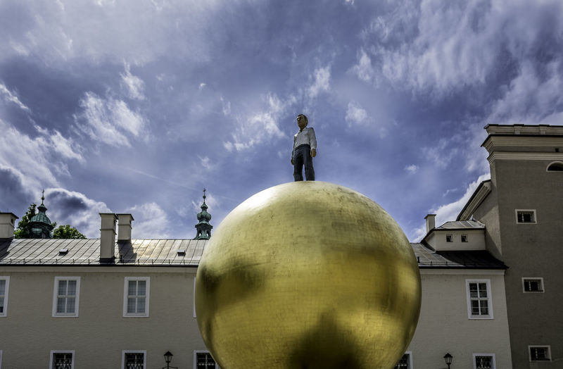 The man standing on a golden sphere in Salzburg Austria Ball Europe Golden Goldene Kugel Landmark Man Salzburg Sphere Tourist Österreich