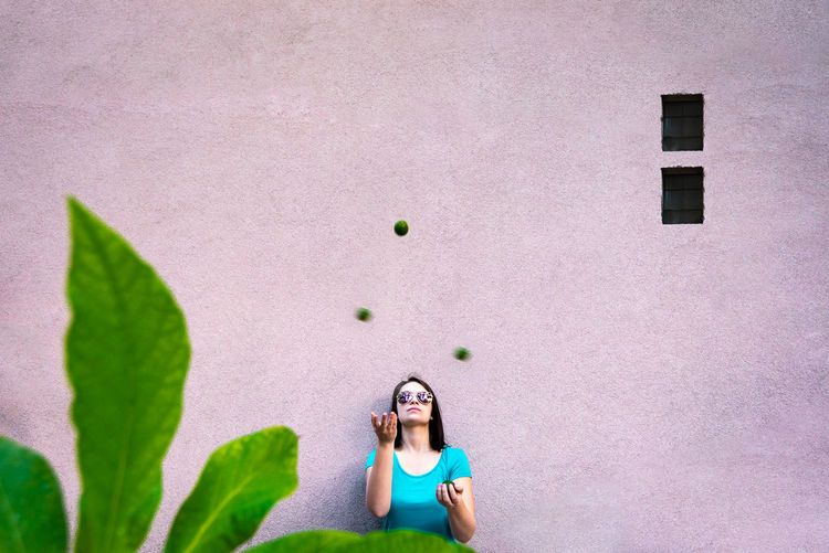 Woman looking up against pink wall