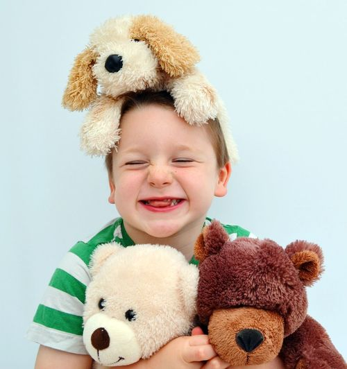 Smiling Boy With Toys Against White Background