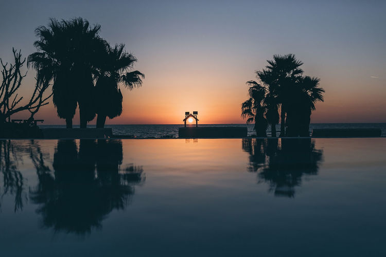 Silhouette palm trees by swimming pool against sky during sunset