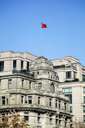 Low angle view of chinese flag on government building against clear blue sky