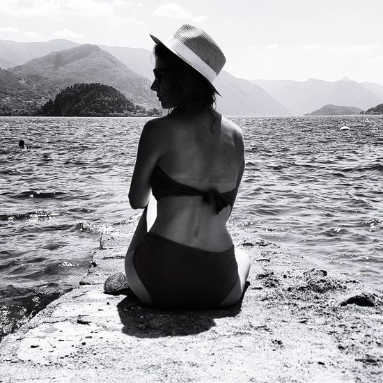 Rear view of woman standing in sea against mountains