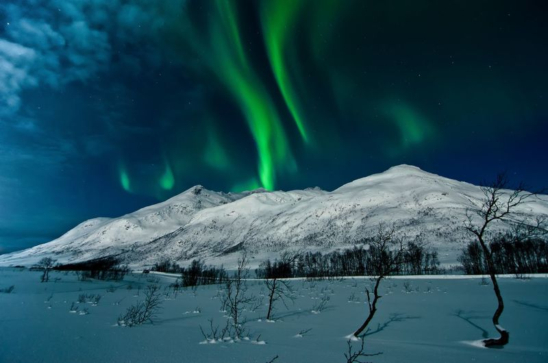 Scenic view of snowcapped mountains at night