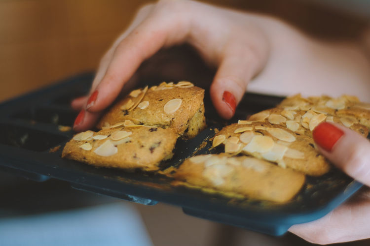 Cropped hands of woman holding cookies in tray