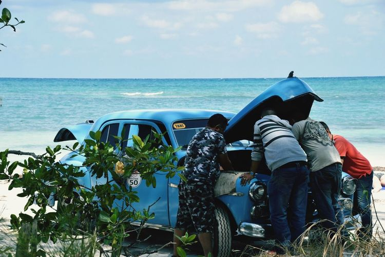 A gathering of Cubans trying to fix a stranded 60's car, on a beach with crashing waves Horizon Over Water Rear View Sky Real People Men Nature Havana Old Car Beachphotography Vintage Cars Water Scenics Lifestyles Beauty In Nature Outdoors Cloud - Sky Togetherness Beach Women Sitting Adult