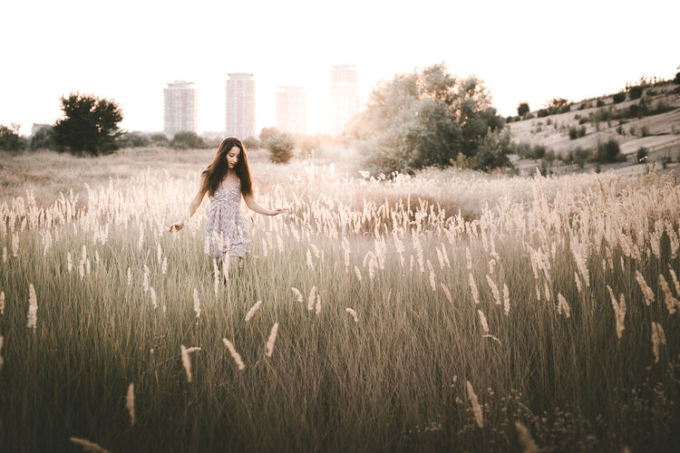 Beauty Girl Outdoors enjoying nature. Beautiful Teenage Model girl in floral dress running on the Spring Field, Sun Light. Building Exterior Day Field Full Length Grass Growth Nature One Person Outdoors People Plant Sky Tree This Is Natural Beauty