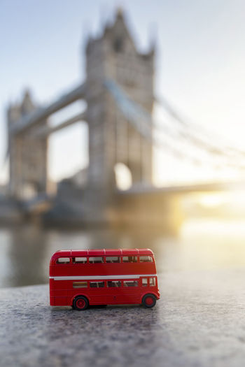 London travel concept: a red double decker bus miniature in front of the Tower Bridge during sunrise Red Built Structure Architecture Transportation Building Exterior Mode Of Transportation City Travel Focus On Foreground Travel Destinations Toy Car Bridge Day London Concept Double Decker Bus Tourism Tourist Attraction  Travel Sunrise Morning Toy Miniature Landmark Attraction