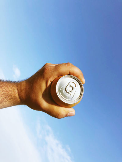 Low angle view of hand holding drink against blue sky