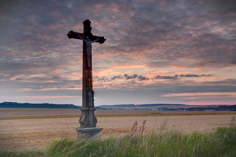 Cross On Agricultural Field Against Sky During Sunset