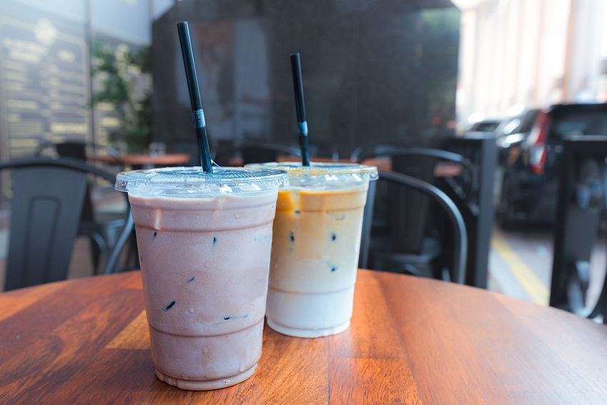 Iced Mocha and Iced Latte coffee drinks in clear plastic cups with straws on outdoor wooden table outside a cafe. Ice Mocha Iced Coffee Cafe Close-up Cold Temperature Day Disposable Cup Drink Drinking Glass Drinking Straw Food And Drink Freshness Healthy Eating Ice Latte Indoors  No People Plastic Straws Refreshment Table Table Top ıced Coffee