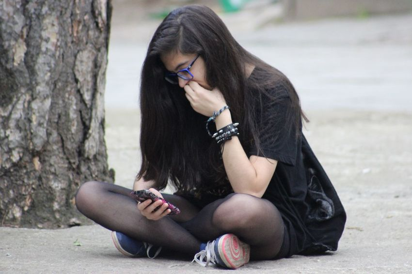 Beauty Black Hair Brown Hair Casual Clothing Day Fashion Focus On Foreground Hand In Hair Leisure Activity Lifestyles Long Hair Medium-length Hair Outdoors Sensuality Sitting Smartphone The Street Photographer - 2016 EyeEm Awards Young Adult Young Women Girl Power