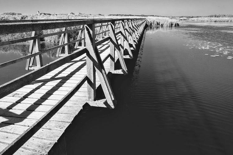Pier on bridge over river against sky