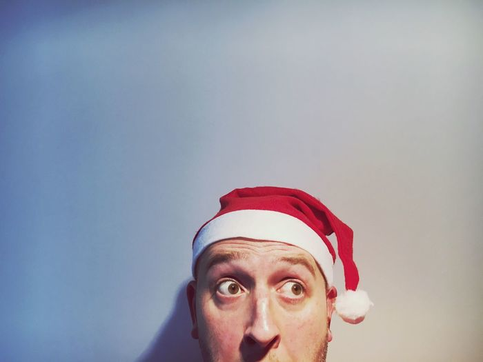 Man looking away in santa hat against white background