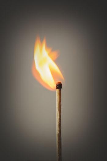 Close-Up Of Illuminated Match Stick Against Gray Background