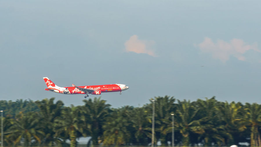 Low angle view of red airplane flying against sky