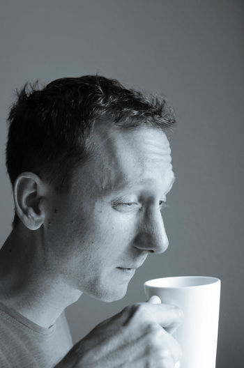 Man Having Coffee Against Wall