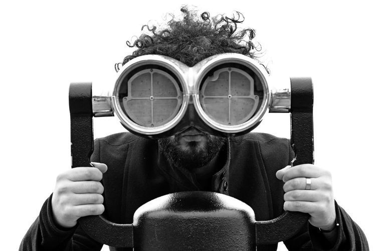 Portrait Of Man Looking Through Coin-Operated Binoculars Against Clear Sky
