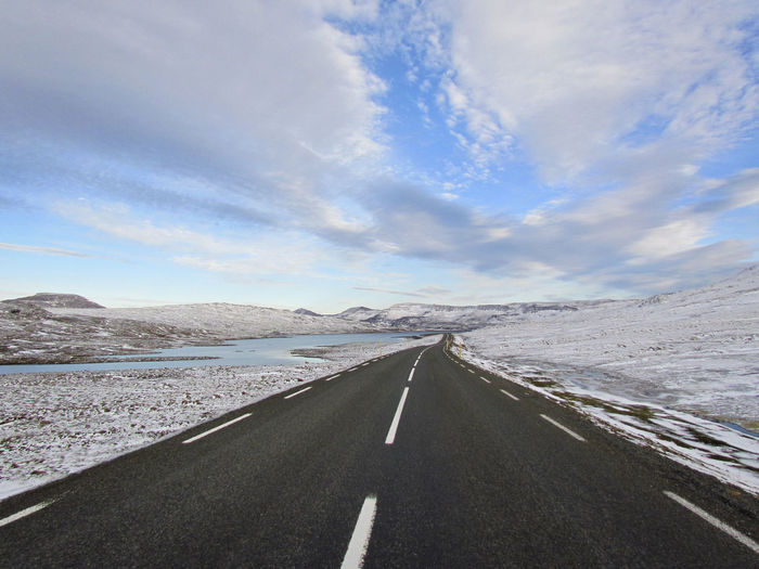 Empty asphalt road through snow covered landscape in iceland