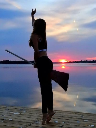 Playful woman holding broom while jumping on pier by lake during sunset