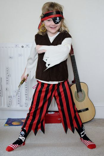 Full length portrait of girl in pirate costume standing at home