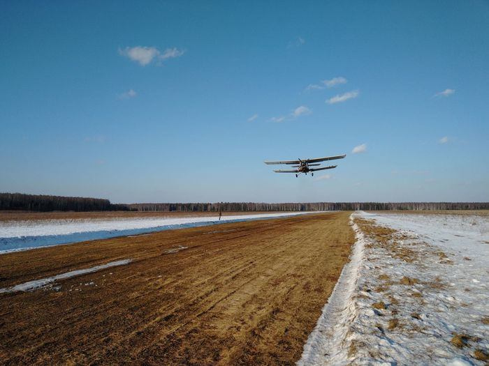 Airplane flying over landscape against blue sky