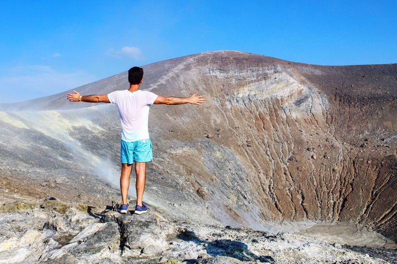 Rear view of man with arms outstretched standing at volcano