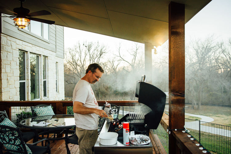 Man cooking food on barbeque at porch
