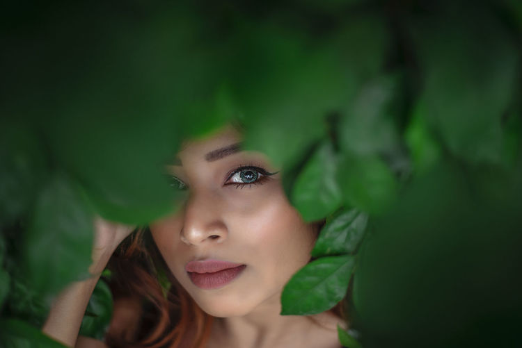 Close-up portrait of young woman by leaves