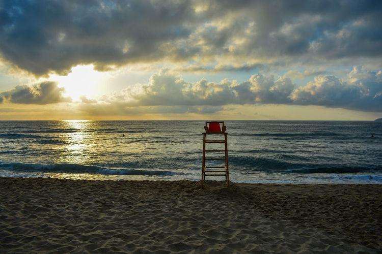 Ladder on beach against cloudy sky during sunset