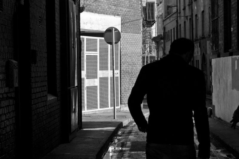 Rear view of a man walking down alley
