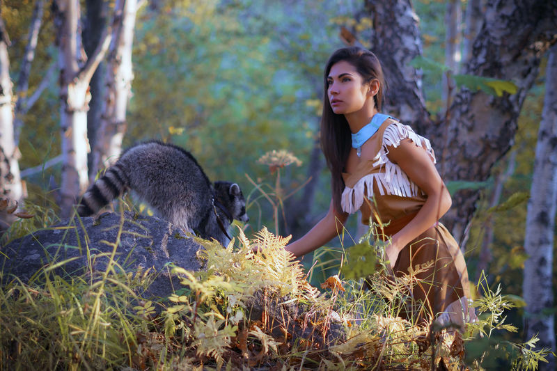 Young Woman In Traditional Clothing Standing By Raccoon In Forest