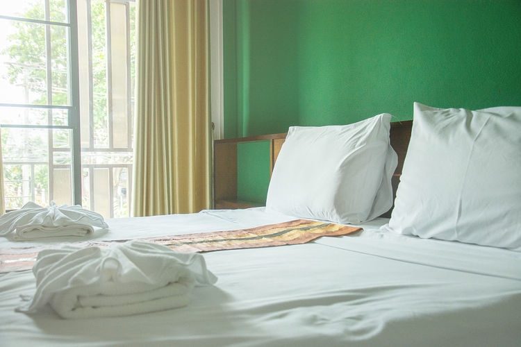 White pillows and white towels on bed in green wall room Absence Bed Bedroom Blanket Clean Comfortable Cozy Curtain Domestic Life Domestic Room Duvet Furniture Home Interior Hotel Room Indoors  Linen Messy No People Pillow Pillows Sheet Textile Towels White Color Window